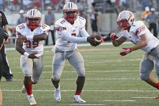 Rocket quarterback Julon Williams gets the ball to Jay Miller (right) after a fake to Rashad Wisdom as Judson plays Lake Travis at Cavalier Stadium in Austin on August 26, 2016