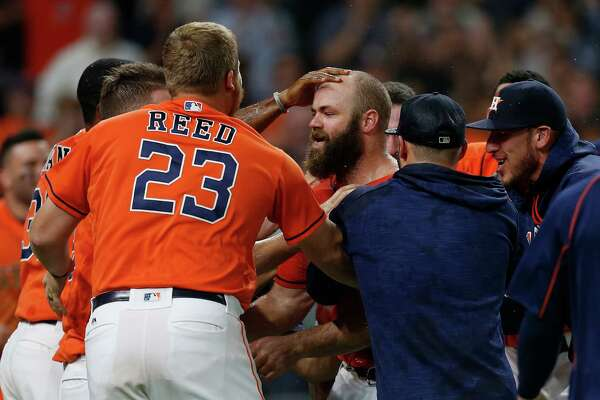 Houston Astros designated hitter Evan Gattis (11) is mobbed at the plate after his walk off home run during the ninth inning of an MLB game at Minute Maid Park, Friday, Aug. 26, 2016 in Houston.