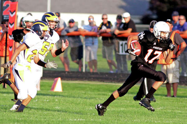 Paul P. Adams/Huron Daily Tribune   Harbor Beach's Brenden Shedd (17) breaks away from a pair of Bad Axe defenders on his way to a 72-yard touchdown in the first quarter of the Pirates' 64-44 win, Friday night, in Harbor Beach.