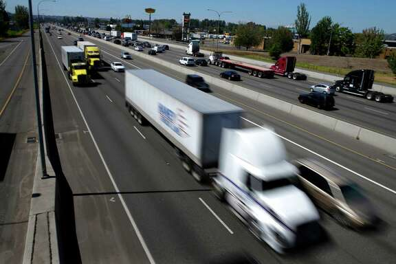 In this Wednesday, Aug. 24, 2016, photo, truck and automobile traffic mix on Interstate 5, headed north through Fife, Wash., near the Port of Tacoma. The federal government wants to limit how fast trucks, buses and other large vehicles can drive on the nation's highways. A new regulation posted Friday, Aug. 26, would impose the nationwide limit by electronically capping speeds with a device on newly-made U.S. vehicles that weigh more than 26,000 pounds. (AP Photo/Ted S. Warren)