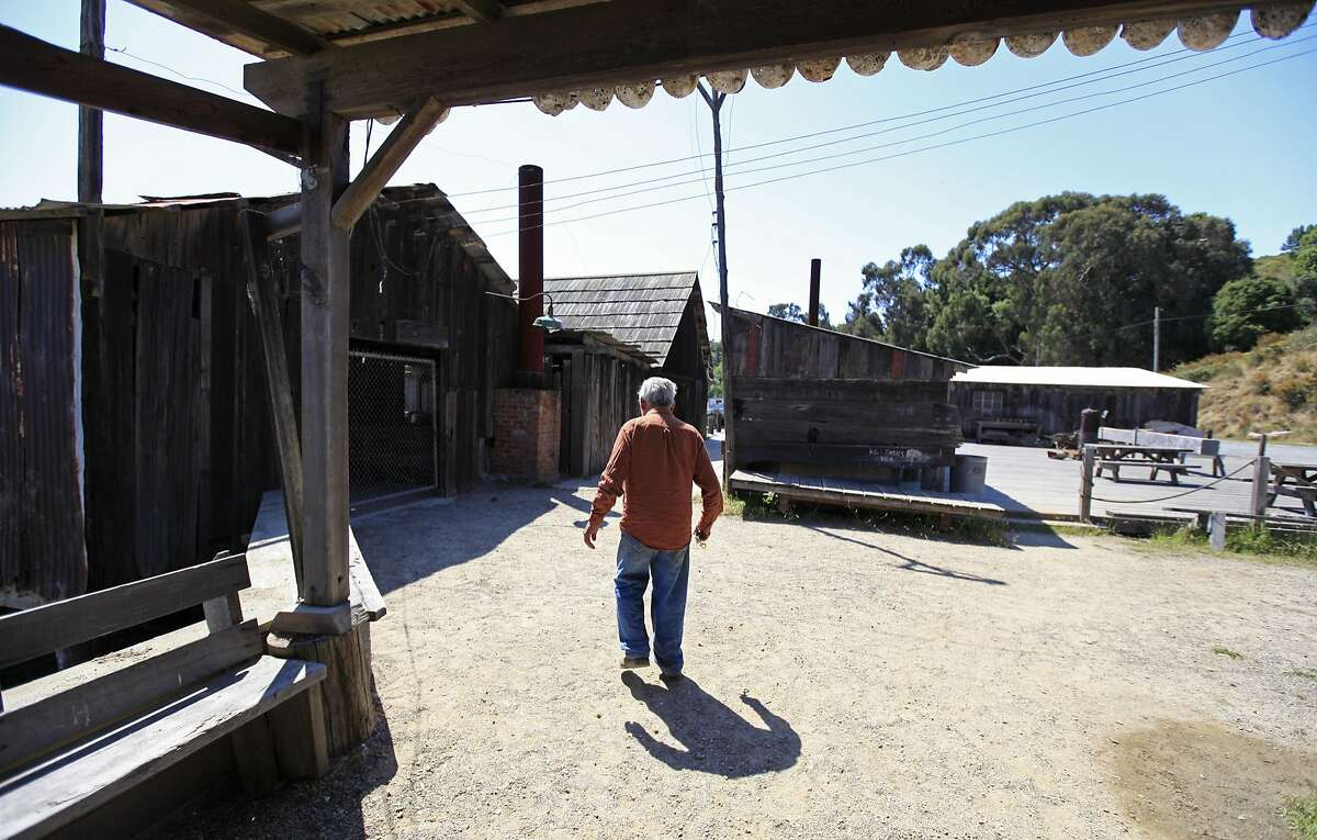 FILE - In this file photo taken Friday, July 15, 2011, park resident Frank Quan walks to open the gate to the pier at China Camp State Park, Calif. Quan, the last of the China Camp shrimpers, the remaining resident of a shrimping village established by Chinese immigrants on the northern shore of San Francisco Bay, died on Aug. 15, 2016. He was 90. (AP Photo/Eric Risberg, File)