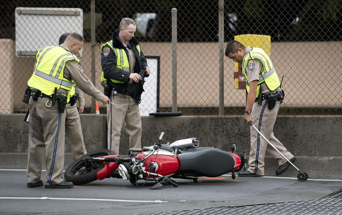 California Highway Patrolmen investigate the scene where a crashed Ducati motorcycle lay on the north end of the Golden Gate Bridge on Friday, August 26, 2016. The solo motorcycle crash resulted in the fatality of the driver and snarled traffic on both sides of the bridge.