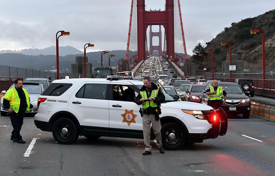 A California Highway Patrol officer (C) takes photos with his cell phone of scene where a crashed Ducati motorcycle lay on the north end of the Golden Gate Bridge on Friday, August 26, 2016. The solo motorcycle crash resulted in the fatality of the driver and snarled traffic on both sides of the bridge. Photo: Josh Edelson / Special To The Chronicle