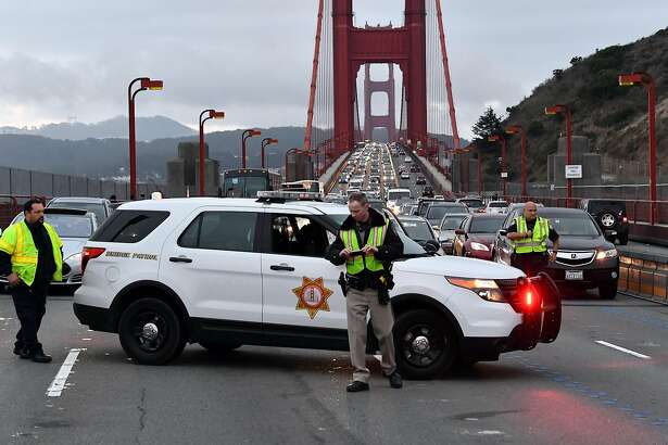 A California Highway Patrol officer (C) takes photos with his cell phone of scene where a crashed Ducati motorcycle lay on the north end of the Golden Gate Bridge on Friday, August 26, 2016. The solo motorcycle crash resulted in the fatality of the driver and snarled traffic on both sides of the bridge.