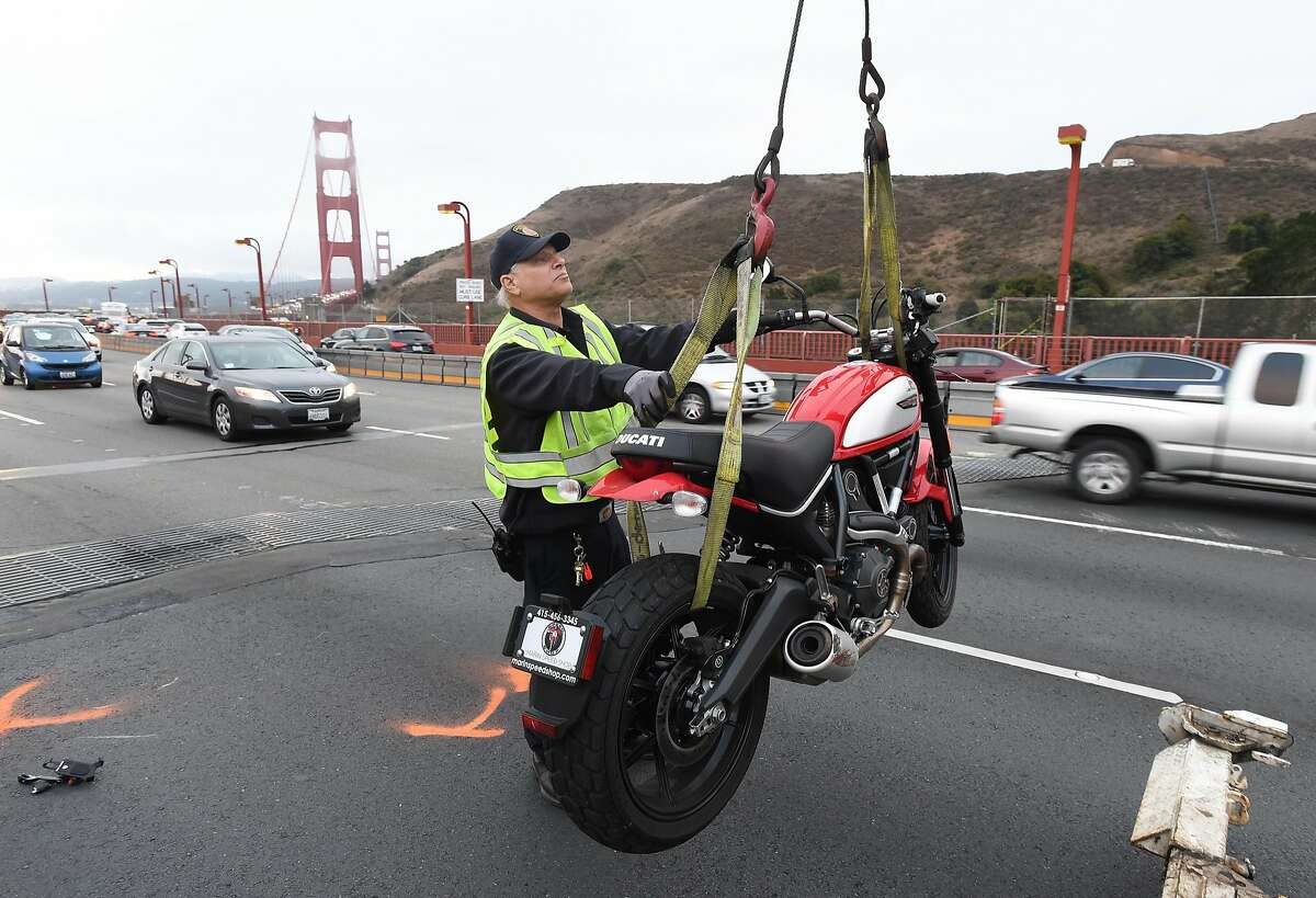 A Golden Gate Bridge serviceman helps load a crashed Ducati motorcycle onto a tow truck on the north end of the Golden Gate Bridge on Friday, August 26, 2016. The solo motorcycle crash resulted in the fatality of the driver and snarled traffic on both sides of the bridge.