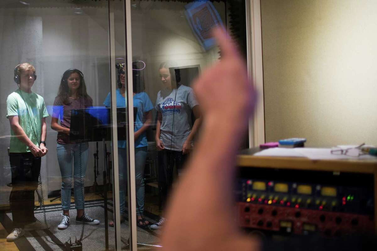 Scott Szabo raises his hand to direct a group of teenage singers, Joseph Cahill, 14, Zoe Marquez, 14, Miranda Marquez, 14, and Rachel Marquez, 14, during the recording of a car dealership jingle commercial at zabo Sound and Music, Friday, Aug. 19, 2016, in Houston. ( Marie D. De Jesus / Houston Chronicle )