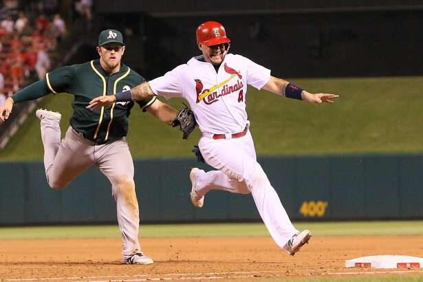St. Louis Cardinals' Yadier Molina (right) is tagged out by Oakland Athletics second baseman Max Muncy as he tries to retreat to first base on a sacrifice fly off the bat of Cardinals' Jhonny Peralta to end the sixth inning during a game between the St. Louis Cardinals and the Oakland Athletics on Friday, Aug. 26, 2016, at Busch Stadium in St. Louis. (Chris Lee/St. Louis Post-Dispatch/TNS)