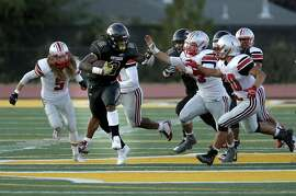 Antioch's Najee Harris, 2 fights off defenders on a 56 yard touchdown run in the first quarter as the Antioch High School Panthers take on the Trojans of Lincoln (Stockton) High in the season opener in Antioch, California on Fri. August 26, 2016.