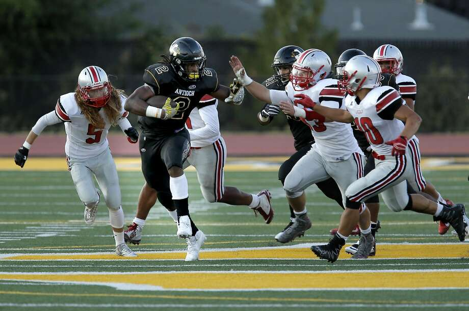 Antioch High's Najee Harris fights off defenders on a 56-yard touchdown run in the first quarter as the Panthers romp on the Trojans of Lincoln (Stockton) High in the season opener in Antioch. Photo: Michael Macor, The Chronicle