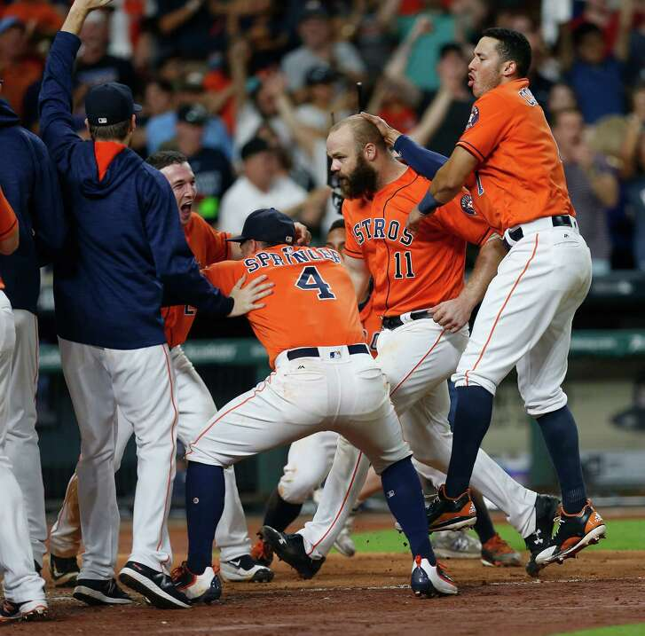 Astros slugger Evan Gattis (11) is mobbed at the plate after his walkoff homer in the ninth inning.
