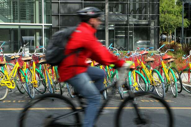 A cyclist makes his way around during Bike to Work Day at the Googleplex, Thursday, May 14, 2015, in Mountain View, Calif. In January 2013, Google raised its default investment for auto-enrolled workers to 10 percent of compensation from 6 percent, according to BrightScope, which rates 401(k) plans.