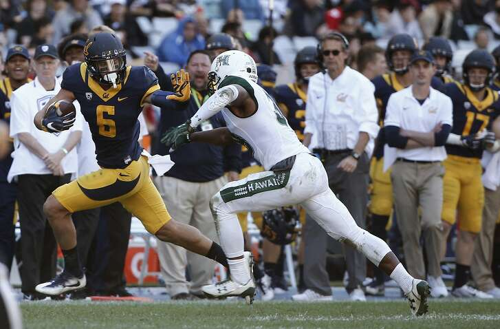 California Golden Bears wide receiver Chad Hansen, left, palms off Hawaii Warriors defensive back Trayvon Henderson during the opening game of the U.S. College football season in Sydney, Australia, Saturday, Aug. 27, 2016. The last American football of any kind played in Sydney was an NFL preseason game at the Olympic stadium that attracted 73,000 spectators in 1999. (AP Photo/Rob Griffith)