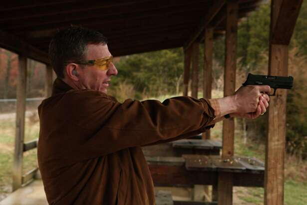 Rob Schenck shoots a pistol in a scene from the documentary Armor of Light.