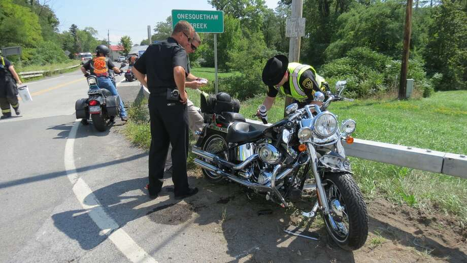 Albany Sheriff Craig Apple, in black, looks on as members of the sheriff's office examine a motorcycle a man was driving before he lost control of the vehicle in Clarksville and died in the subsequent crash. (Thomas Heffernan Sr. / Times Union) Photo: Picasa