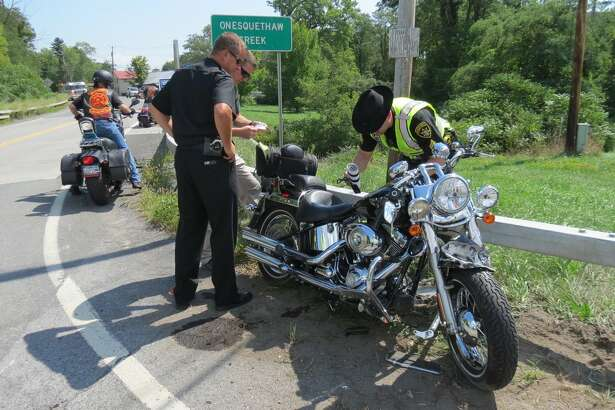 Albany Sheriff Craig Apple, in black, looks on as members of the sheriff's office examine a motorcycle a man was driving before he lost control of the vehicle in Clarksville and died in the subsequent crash. (Thomas Heffernan Sr. / Times Union)