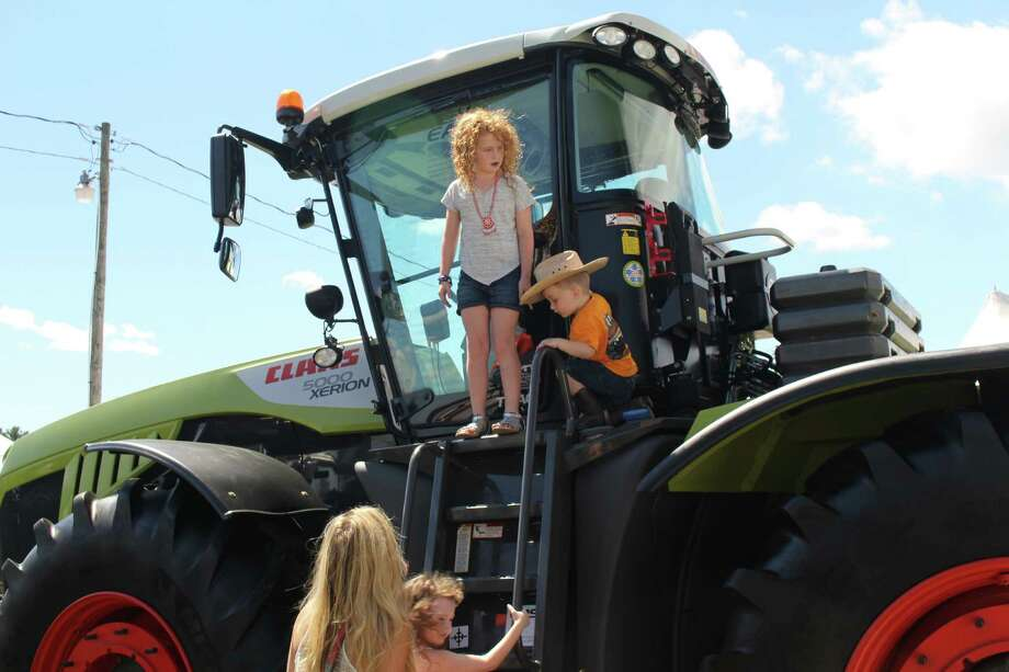 """Young visitors check out a Claas, the German-made $500,000 """"Mercedes Benz of farm tractors"""" on Tuesday, Aug. 23, 2016, at the Washington County Fairgrounds during this year's fair. (Bob Gardinier)"""