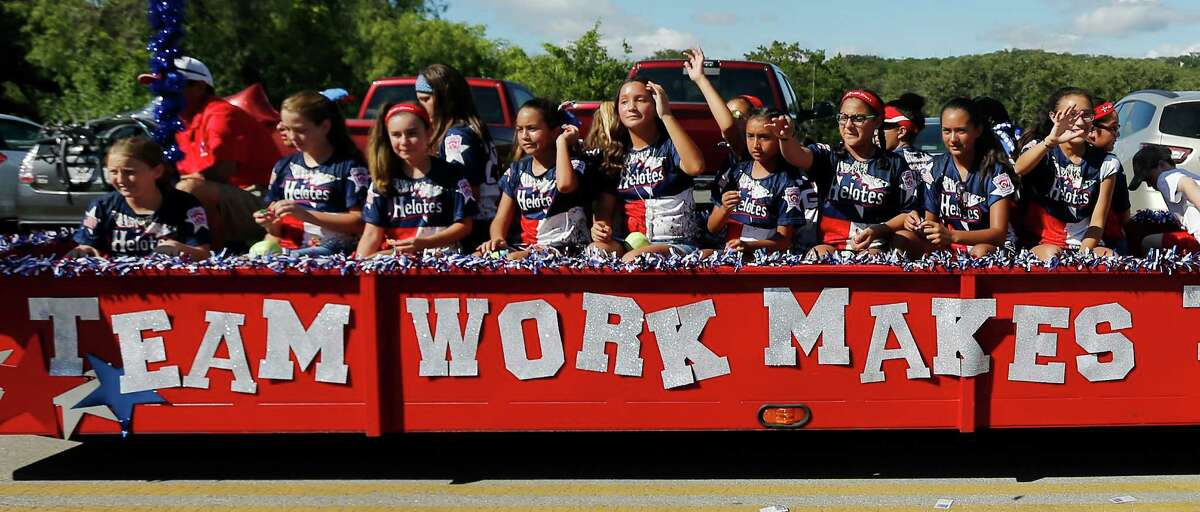 Players from the 9 to 11-year-old teams also took part in the parade as supporters and fans of the Greater Helotes Little League softball team lined Old Bandera Road to cheer the team of girls who were crowned the 2016 Little League Softball World Series Champions during a parade in their honor on Saturday, Aug. 27, 2016. A small procession of fire trucks, local businesses and small-town royal courts led the parade but the biggest cheers came for 13 young women who captured the coveted title of world champions.