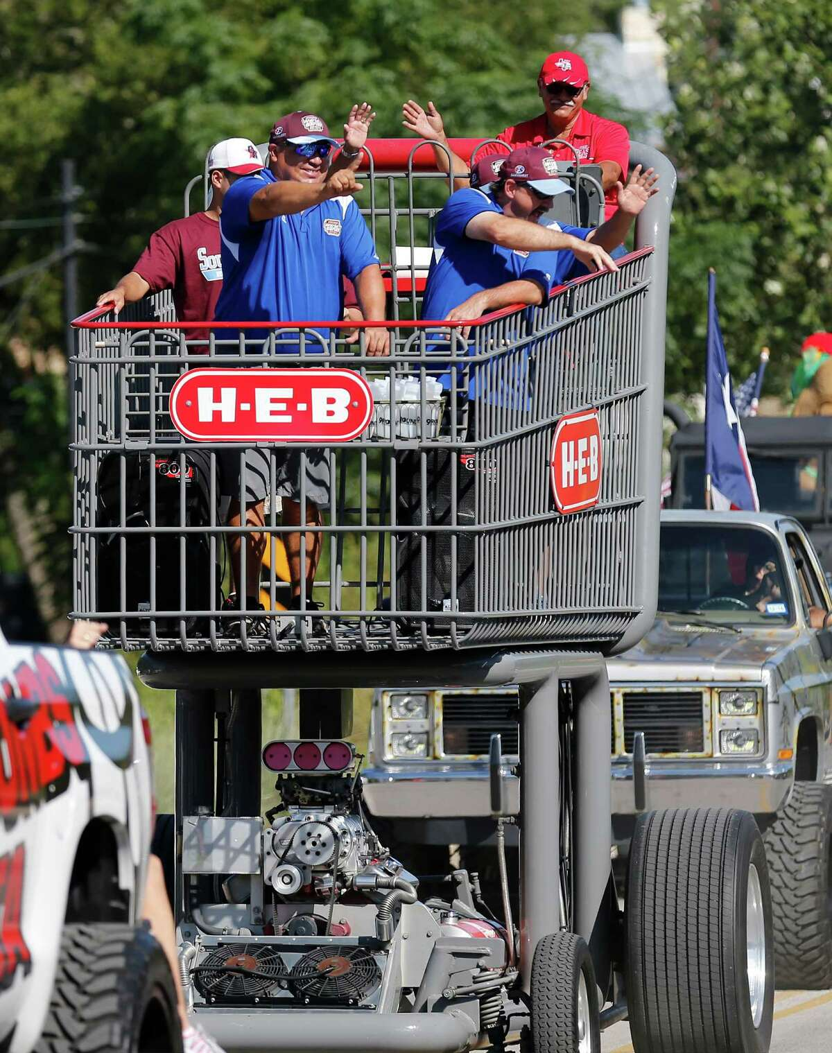 Head coach Mario Sanchez (foreground) along with assistants Matt Norman and Frank Ball get a ride in an over-sized shopping cart as supporters and fans of the Greater Helotes Little League softball team lined Old Bandera Road to cheer the team of girls who were crowned the 2016 Little League Softball World Series Champions during a parade in their honor on Saturday, Aug. 27, 2016. A small procession of fire trucks, local businesses and small-town royal courts led the parade but the biggest cheers came for 13 young women who captured the coveted title of world champions.
