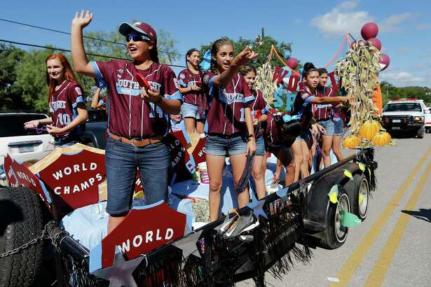 Olivia Ball (10), Annika Litterio (14), Jada Munoz (11) and the other members of the Greater Helotes Little League softball team wave and toss treats to supporters and fans during a parade along Old Bandera Road in Helotes to honor the team of girls who were crowned the 2016 Little League Softball World Series Champions on Saturday, Aug. 27, 2016. A procession of fire trucks, local businesses and small-town royalty led the parade but the biggest cheers came for 13 young women who captured the coveted title of world champions earlier in the month.