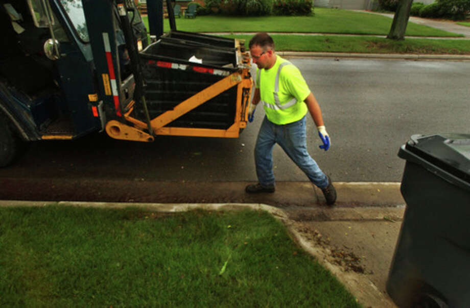 In this file photo, a City of Midland Public Works employee collects refuse from a residential area to deposit in a dual stream front load truck. Midland City Council voted Monday, Aug. 22  to approve a purchase order for $1,179,100, in order to replace four refuse trucks.
