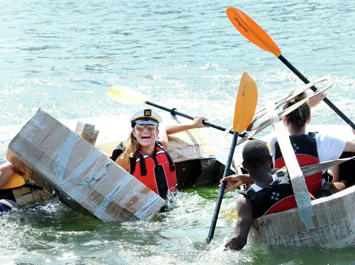 Kelly Aneson, of Edison, N.J., ended up in the water as her kayak SS Harambe sunk during the SoundWaters HarborFest 16 cardboard kayak race on Stamford Harbor Saturday.