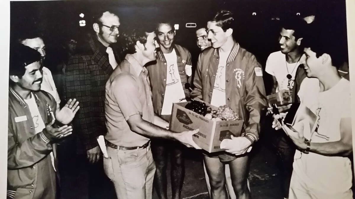 In the summer of 1976, tying the nations bicentennial to reawakening the country's spiritual values,Jim Miccio and about 30 other young men set out on a cross-country relay run through the 48 contiguous states. One of those young men, Ken (Mohan) Peck, right, receives a fruit basket in one of the many towns that gave them gifts along the route. Jim Miccio is to the town resident's immediate left.
