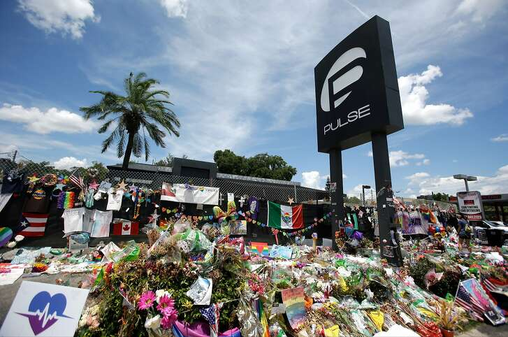 This Monday, July 11, 2016 photo shows a makeshift memorial outside the Pulse nightclub, a month after the mass shooting in Orlando, Fla. The more than 430 fundraisers posted on the GoFundMe website after the attack have exposed weaknesses inherent in these popular do-it-yourself charity campaigns: waste, questionable intentions and little oversight. (AP Photo/John Raoux)