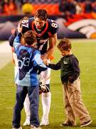 DENVER POST PHOTO BY CYRUS MCCRIMMON 12/29/02 INVESCO FIELD AT MILE HIGH  After the game Broncos WR 87 Ed McCaffrey greets his sons  Max McCaffrey (left) and Christian McCaffrey on the field.. Broncos They won 37-7.