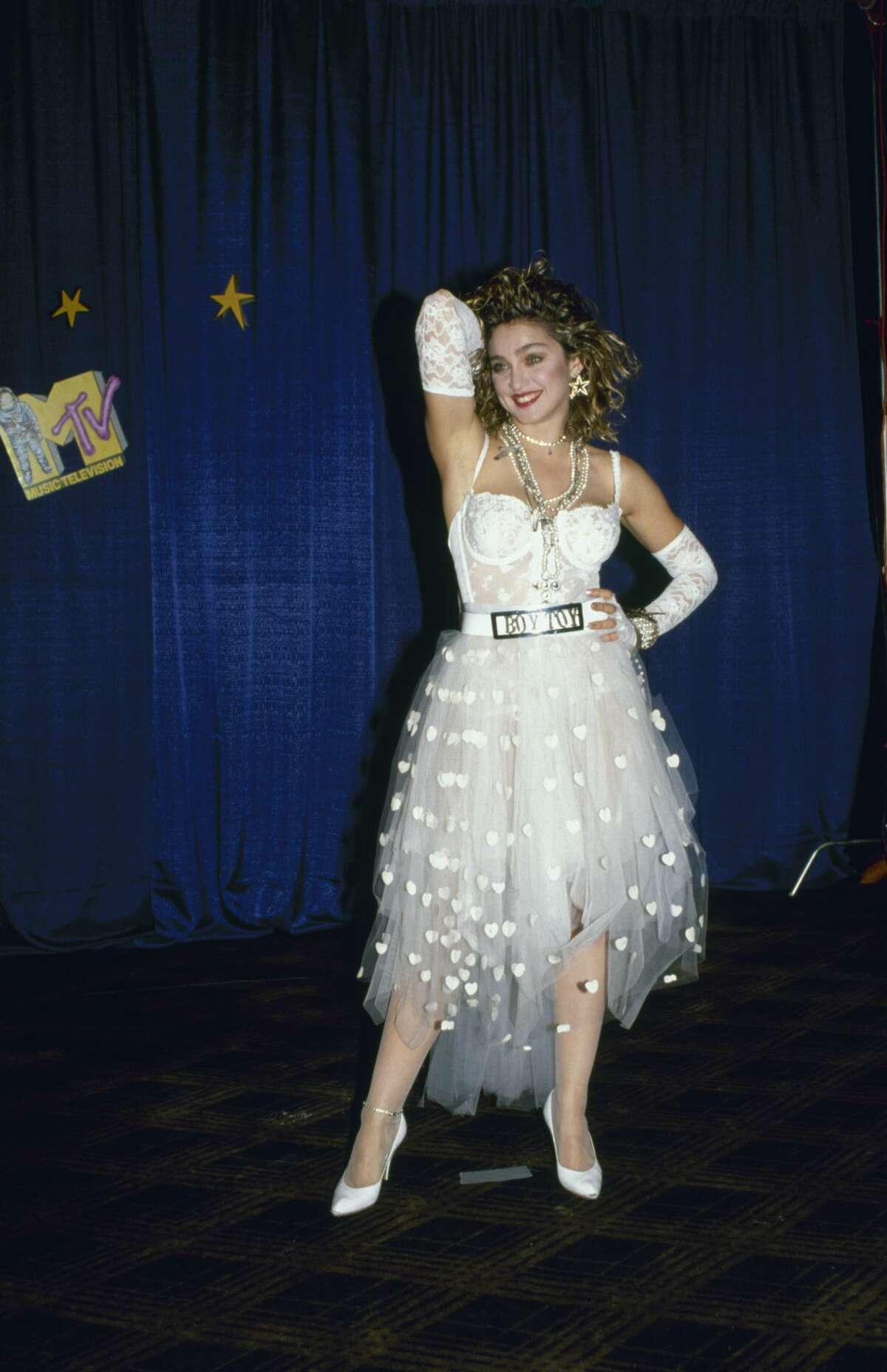 1984:American singer and actress Madonna, dressed in white lace lingerie, pearls, and a 'Boy Toy' belt buckle, stands with one hand on her head and one on her hip at First Annual MTV Video Music Awards.
