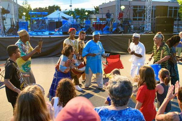 "Chicago based fusion band ""Funkadesi"" in a Congo line with the crowd in downtown Midland Friday evening."