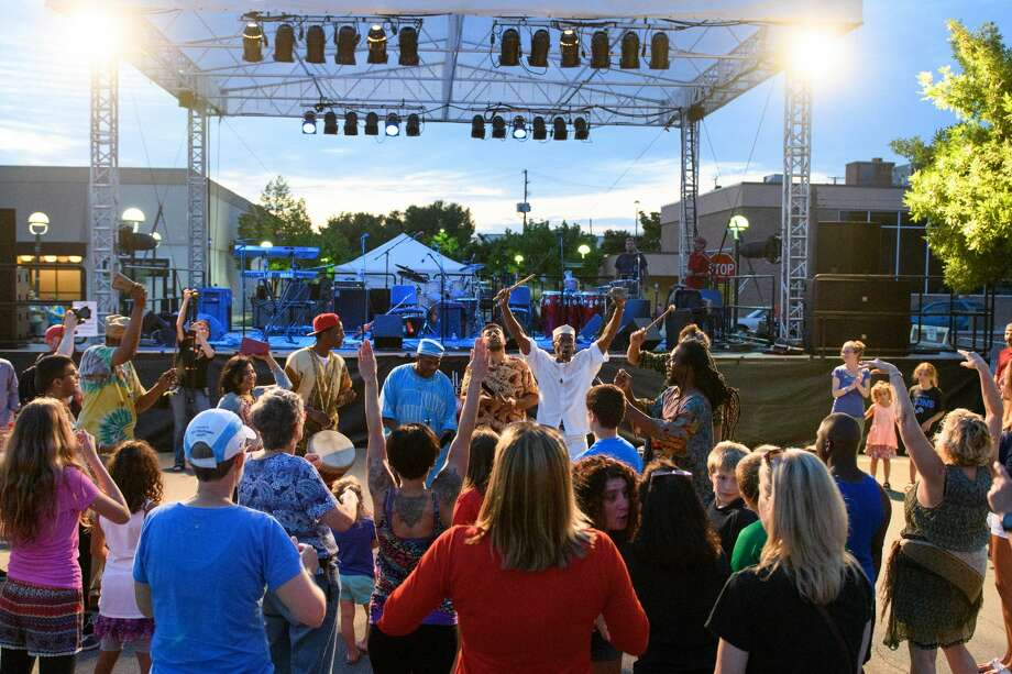 "Chicago based fusion band ""Funkadesi"" in a Congo line with the crowd in downtown Midland Friday evening. Photo: Steven Simpkins/Midland Daily Ne/Steven Simpkins"