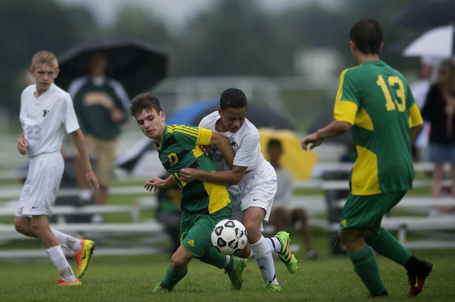 Dow High's Cody Glazier, left, and Freeland's Ben Younglao fight for possession of the ball in the second half of a game against Freeland during the Dow High soccer tournament Saturday afternoon. Photo: Brittney Lohmiller/Midland Daily News/Brittney Lohmiller, Brittney Lohmiller/Midland Daily News