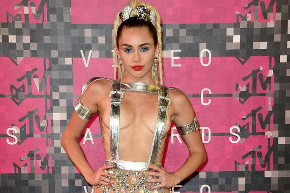 2015:  Host Miley Cyrus, styled by Simone Harouche, wearing a custom Versace outfit and boots,  attends the 2015 MTV Video Music Awards at Microsoft Theater on August 30, 2015 in Los Angeles, California.