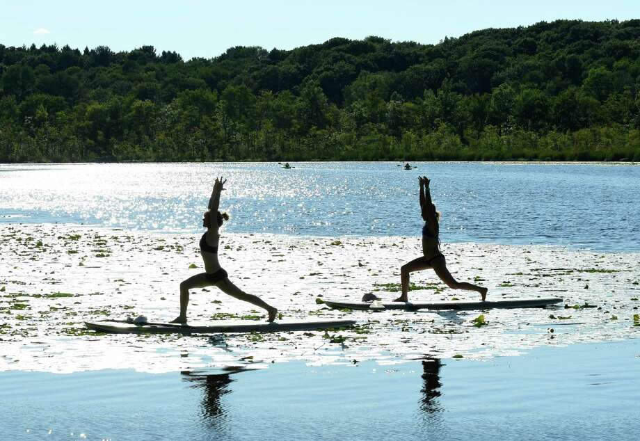 SUP Yoga instructor Rhiana Stallard, left, and Blair Williams take part in some sunset yoga on Saratoga Lake Tuesday Aug. 23, 2016 in Saratoga Springs, N.Y. (Michael P. Farrell/Times Union) Photo: Michael P. Farrell / 20037719A