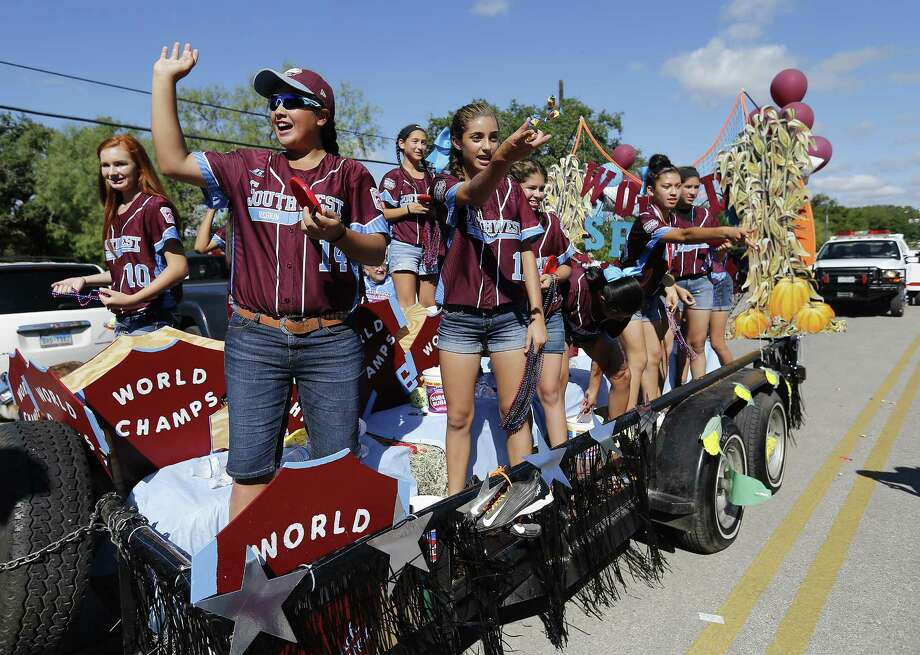 Olivia Ball (10), Annika Litterio (14), Jada Munoz (11) and the other members of the Greater Helotes Little League softball team wave and toss treats to supporters and fans during a parade along Old Bandera Road in Helotes to honor the team of girls who were crowned the 2016 Little League Softball World Series Champions on Saturday, Aug. 27, 2016. A procession of fire trucks, local businesses and small-town royalty led the parade but the biggest cheers came for 13 young women who captured the coveted title of world champions earlier in the month. (Kin Man Hui/San Antonio Express-News) Photo: Kin Man Hui, Staff / San Antonio Express-News / ©2016 San Antonio Express-News