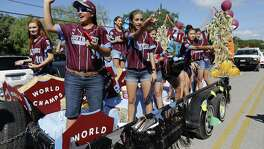 Olivia Ball (10), Annika Litterio (14), Jada Munoz (11) and the other members of the Greater Helotes Little League softball team wave and toss treats to supporters and fans during a parade along Old Bandera Road in Helotes to honor the team of girls who were crowned the 2016 Little League Softball World Series Champions on Saturday, Aug. 27, 2016. A procession of fire trucks, local businesses and small-town royalty led the parade but the biggest cheers came for 13 young women who captured the coveted title of world champions earlier in the month. (Kin Man Hui/San Antonio Express-News)