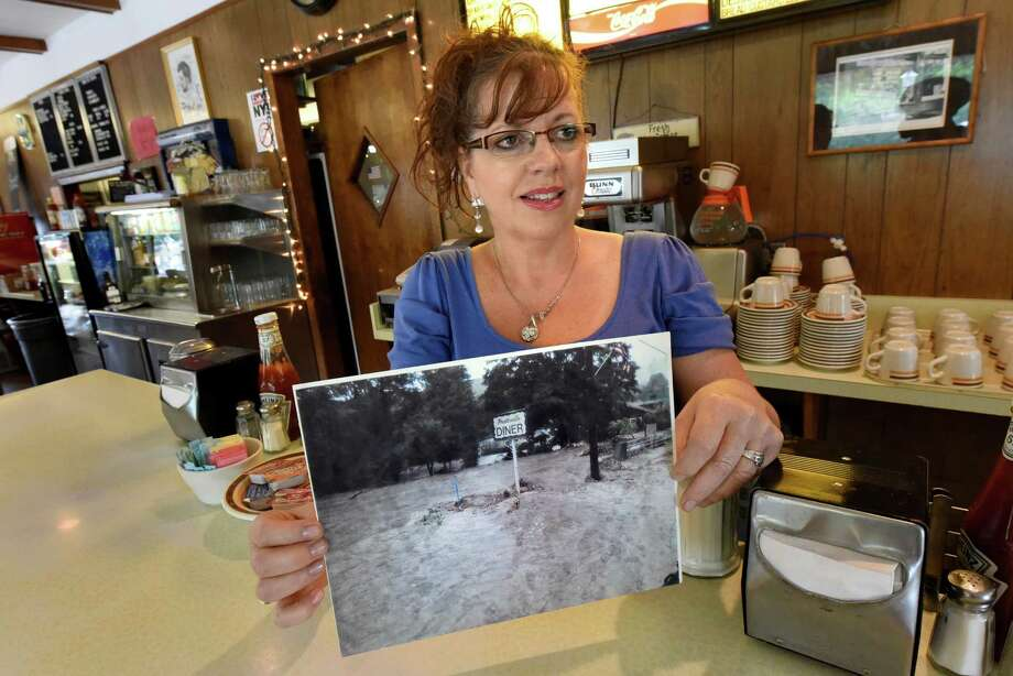 Janelle Maurer, owner of the Prattsville Diner, holds a photo showing flood water from Tropical Storm Irene on Saturday, Aug. 27, 2016, in Prattsville, N.Y. Sunday marks 5 years since the storm devastated the town. (Cindy Schultz / Times Union) Photo: Cindy Schultz / Albany Times Union