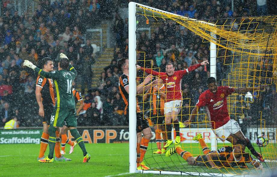 Manchester United's Marcus Rashford (19) scores the game-winner as Wayne Rooney (10) celebrates and Hull goalkeeper Eldin Jakupovic (left) throws up his arms in frustration. Photo: Mark Runnacles, Getty Images