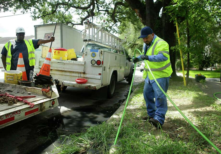 Utility worker Oswaldo Diaz, right, performs a trace on a sewer pipe to find a break in front of a house on Houston Avenue on Thursday. The crew found a hole in the service line where tree roots broke through it. Photo: Mark Mulligan, Staff / © 2016 Houston Chronicle