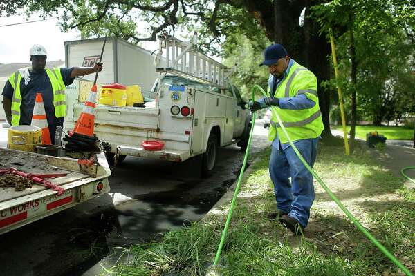 Utility worker Oswaldo Diaz, right, performs a trace on a sewer pipe to find a break in front of a house on Houston Avenue on Thursday. The crew found a hole in the service line where tree roots broke through it.