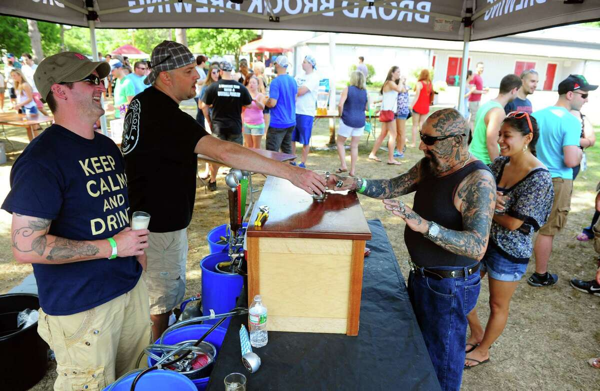 """Nick """"Batso"""" Maccharoli, of Stratford, at right, tries a brew from Broad Brook Brewing Company at the annual ShakesBeer Festival on the grounds of the American Shakespeare Festival Theater in Stratford, Conn. on Saturday August 27, 2016. The festival showcases fine craft beers from around Connecticut as well as nearby states. The event boasts a fantastic line up of both local and regional craft breweries (more than 60 in all); a diverse range of culinary options through several renowned CT Food Trucks and live bands playing classic covers. The event is also a fundraiser for the restoration of the American Shakespeare Theater."""