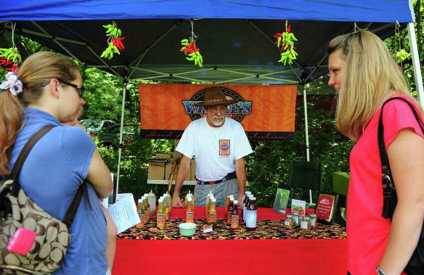 Vendor David Wanke tries to interest a customer in his hot sauce at Greenfield Hill Grange's annual Agricultural Fair on Hillside Road in Fairfield, Conn., on Saturday Aug. 27, 2016. There were farm and agricultural exhibits, grilled and baked goods, live poultry, games, a raffle, pony rides, live music, crafts and jewelry. Some of the exhibits and demonstrations included composting, square foot gardening, raising chickens and antique farm tools.