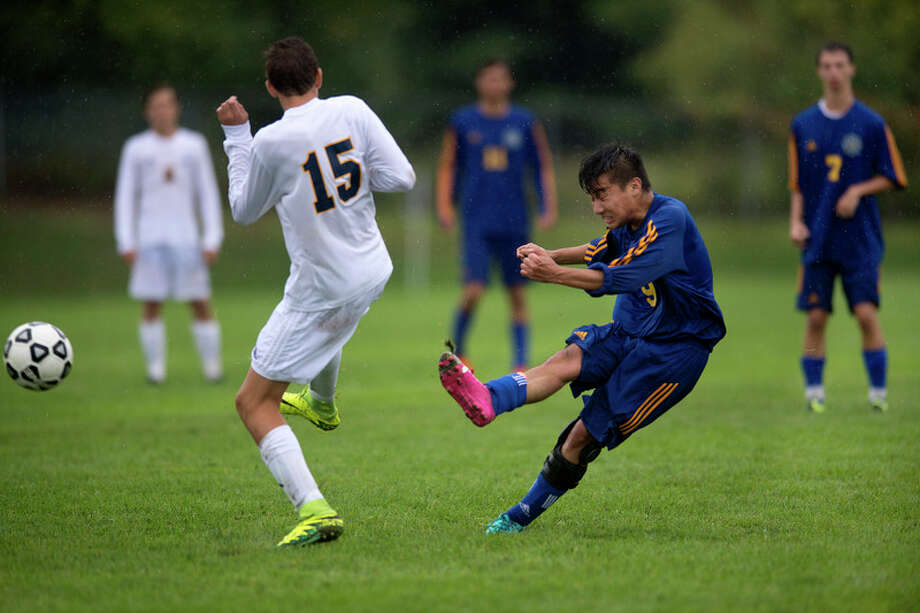 Midland High's Cesar Nakasone kicks the ball down field in the second half on Saturday.