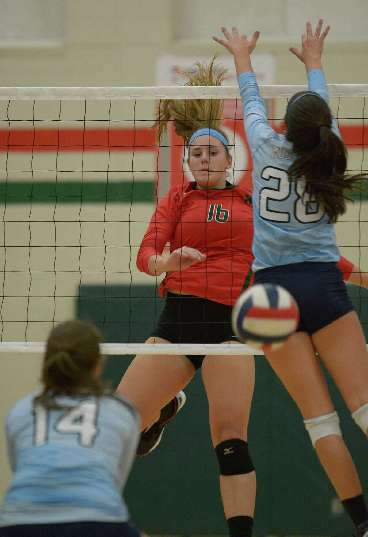 The Woodlands' AJ Koele (16) slams the ball past Kingwood sophomore outside hitter Peyton Shamp (28) during their pre-district matchup at TWHS on August 24, 2016. (Photo by Jerry Baker/Freelance)