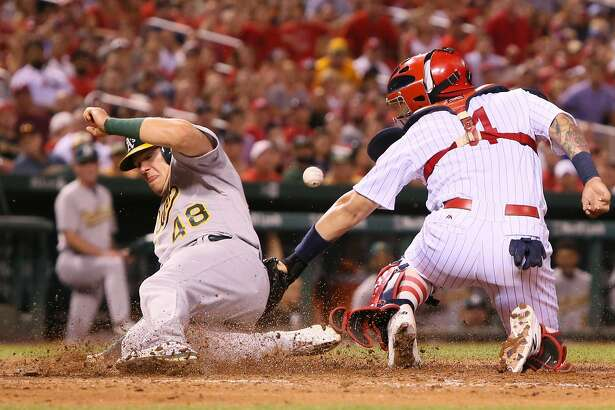 St. Louis Cardinals catcher Yadier Molina is unable to hold onto the throw as Oakland Athletics' Ryon Healy scores the go-ahead run on a sacrifice fly in the eighth inning during a game between the St. Louis Cardinals and the Oakland Athletics on Saturday, Aug. 27, 2016, at Busch Stadium in St. Louis. The Athletics won 3-2. (Chris Lee/St. Louis Post-Dispatch/TSN)