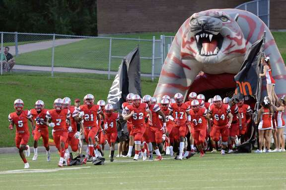 The Travis Tigers football team sprints onto the field at the beginning of the second half of their game against the Heights Bulldogs on Saturday, August 27, 2016 at Mercer Stadium.
