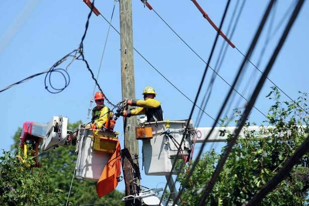 Eversource crews work on a telephone pole on Hope Street in Stamford, Conn. on Sunday, August 28, 2016. The telephone pole was damaged in a rollover crash on Saturday evening.