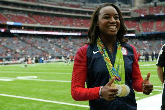 Olympic gold medalist Simone Manuel gives a thumbs up as she stands on the sidelines before the Houston Texans NFL pre-season football game against the Arizona Cardinals at NRG Stadium on Sunday, Aug. 28, 2016, in Houston.
