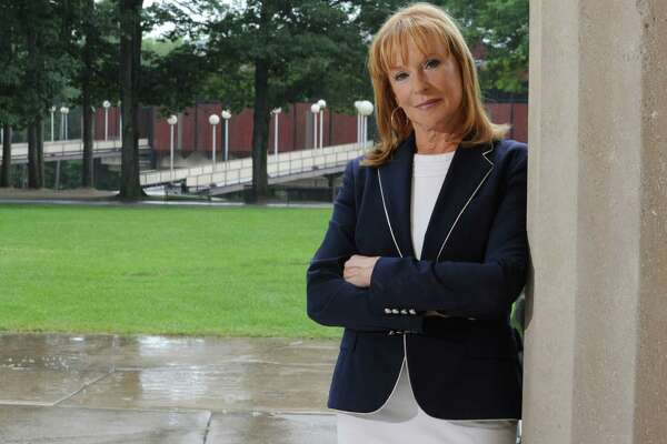 Marcia White, president and executive director of the Saratoga Performing Arts Center, stands against a column at The Hall of Springs where her office is located on Monday, July 28, 2014, at Saratoga Spa State Park in Saratoga Springs, N.Y. This is White's 10th summer at SPAC which is seen in the background. (Lori Van Buren / Times Union)