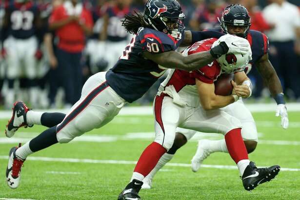 Houston Texans outside linebacker Jadeveon Clowney (90) tackles Arizona Cardinals quarterback Drew Stanton (5) after Stanton was forced out of the pocket for a two-yard gain during the second quarter of an NFL pre-season football game at NRG Stadium on Sunday, Aug. 28, 2016, in Houston.